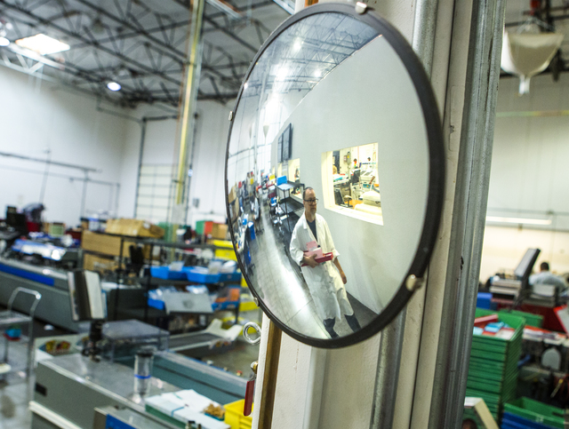 A worker is reflected off a mirror in the secure credit card processing area at Arroweye Solutions in Henderson on Friday, Oct. 21, 2016. The company is the world's largest on-demand credit and de ...