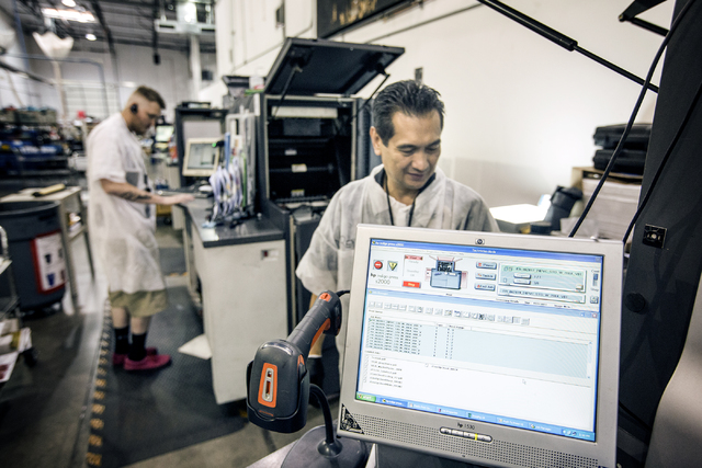 Ray Ungos operates a plastic printer press in the secure credit card processing area at Arroweye Solutions in Henderson on Friday, Oct. 21, 2016. The company is the world's largest on-demand credi ...