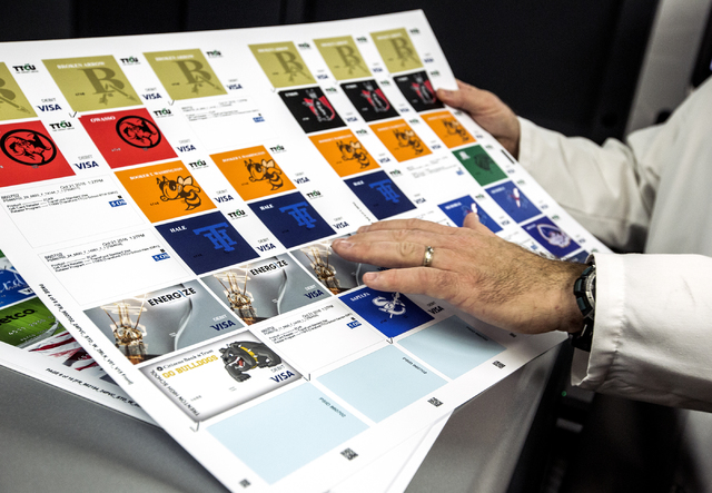 Bob McCormick, vice president for Arroweye Solutions, displays examples of personalized credit card in the secure credit card processing area in Henderson on Friday, Oct. 21, 2016. The company is  ...
