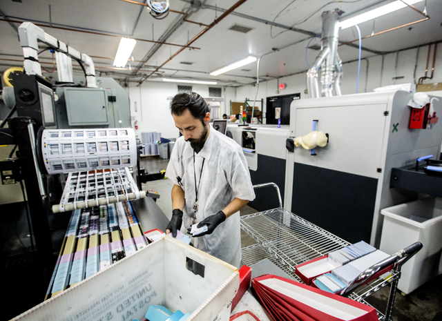 A worker process credit cards in the secure work area at Arroweye Solutions in Henderson on Friday, Oct. 21, 2016. The company is the world's largest on-demand credit and debit producer. (Jeff Sch ...