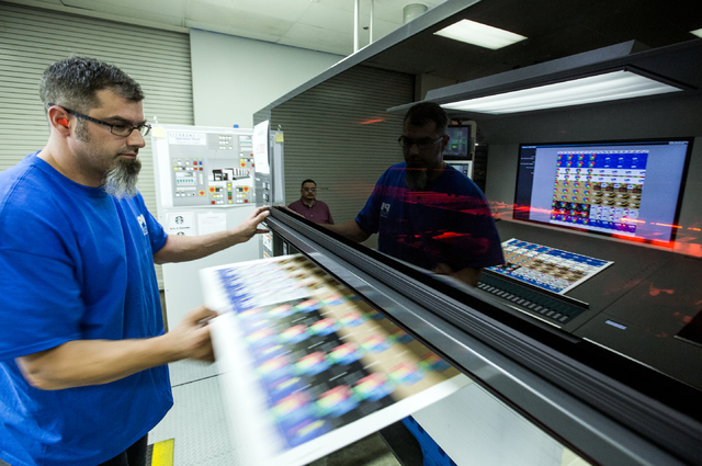 Employee Taylor Oaksmith pulls a sheet of gift cards out of a printing press at Plasticard- Locktech International in North Las Vegas on Monday, Oct. 24, 2016. The keycard manufacturer plans to ad ...