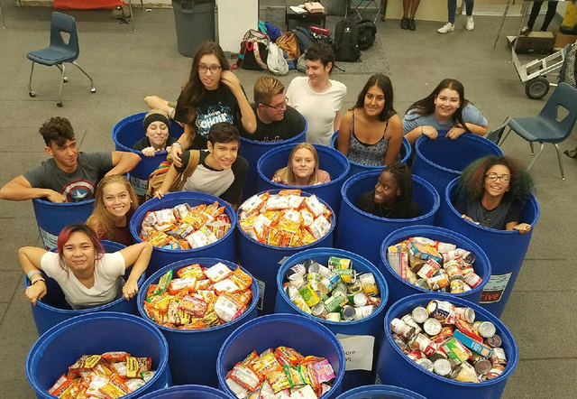 Chaparral High School students sit in buckets behind the non-perishable food they collected during a food drive. Special to View