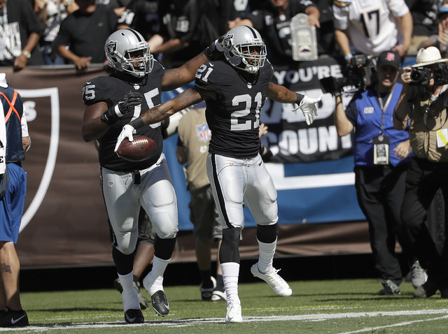 Oakland Raiders cornerback Sean Smith (21) celebrates after intercepting a pass against the San Diego Chargers during the first half of an NFL football game in Oakland, Calif., Sunday, Oct. 9, 201 ...