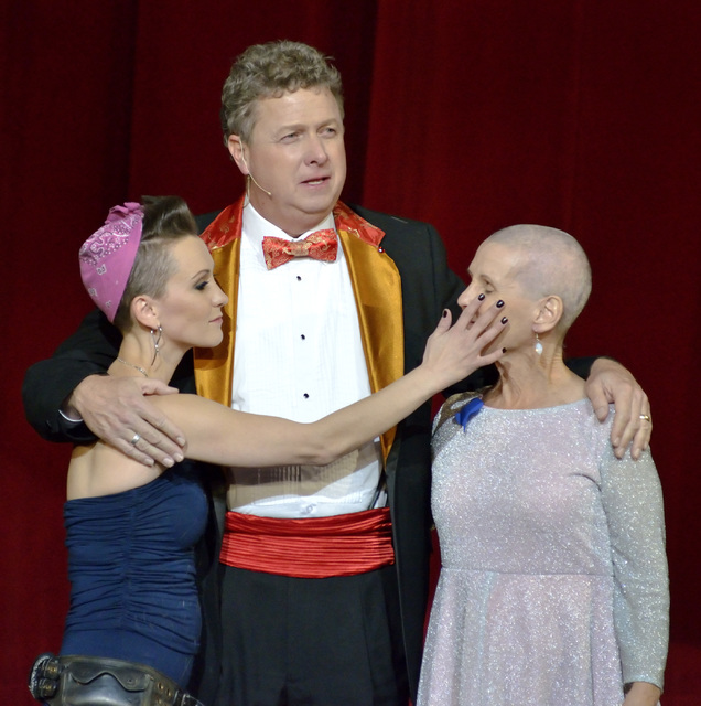 "Erica Linz, left, Christian Kolberg, center, and Erica's mother Mary-Mike Linz are shown after a head shaving ceremony to show solidarity with cancer patients at the Circus Couture "" ..."