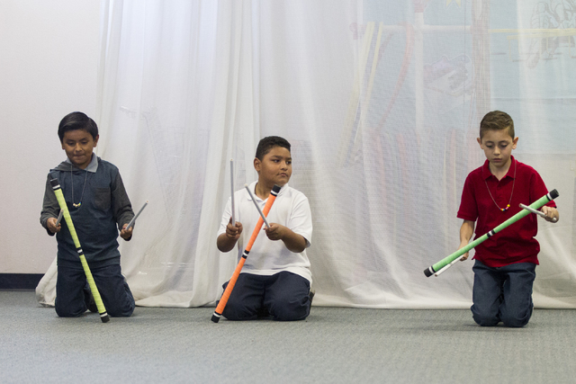 Fourth-grade students Daniel Solis, from left, Daijonn Catala and Gabriel Ramos practice juggling devil sticks during a weekly visit by a teaching artist from Cirque du Soleil's new Arts Nomades p ...
