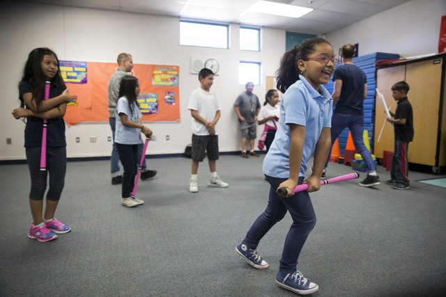 Lissania Sotelo, 8, runs as she helps distribute devil sticks to her fourth-grade classmates at McCall Elementary School during a session with Cirque du Soleil's visiting Arts Nomades teacher. Eri ...
