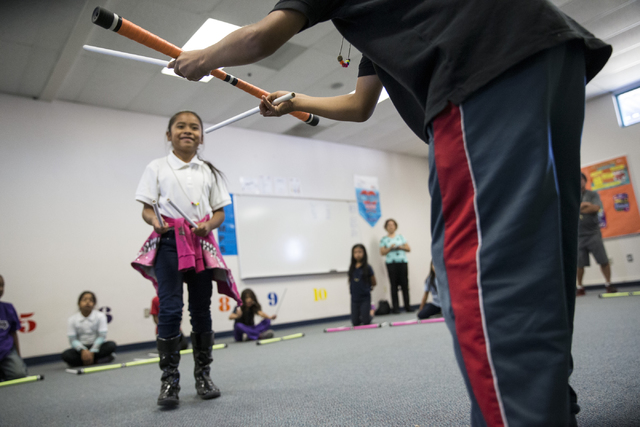 Juggling devil sticks is just one of the circus arts Cirque du Soleil performer Benedikt Negro uses to help fourth-graders at McCall Elementary School learn academic lessons in Cirque's new Arts N ...