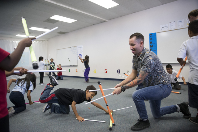 Fourth-grade teacher Richard Savage practices juggling devil sticks with his students during Cirque du Soleil's weekly Arts Nomades program at McCall Elementary School. Erik Verduzco/Las Vegas Rev ...