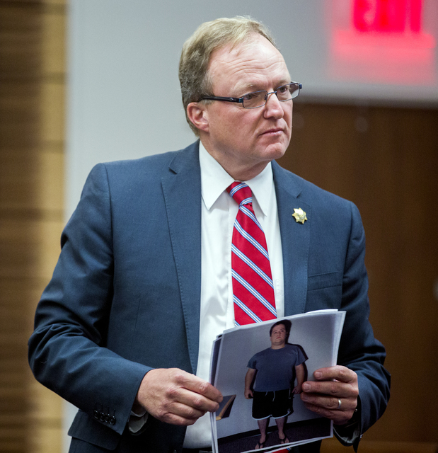 Chief Deputy District Attorney Frank Coumou holds evidence photos of defendant Daron Lewis Clanton during Clanton's preliminary hearing in Henderson Justice Court on Monday, Oct.10, 2016. Clanton  ...