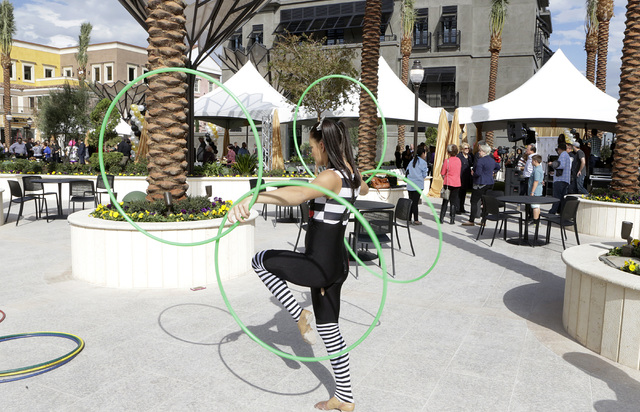 Michelle Bell shows off her circus-style hooping during the ribbon-cutting for the opening of Tivoli Village's second phase Friday, Oct. 28, 2016, in Las Vegas. The second phase added more than 27 ...