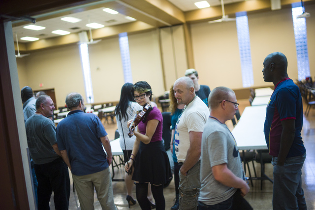 Las Vegas Academy student Geneva Rucker strolls by recovery clients lining up for dinner before she performs as part of the weekly Notes With a Purpose program at the Las Vegas Rescue Mission. Cha ...