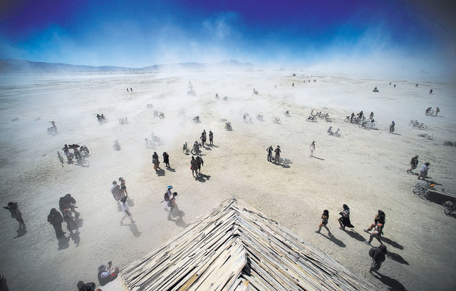 Attendees approach the Catacomb of Veils art installation as dust kicks up along the playa during Burning Man at the Black Rock Desert north of Reno on Thursday, Sept. 1, 2016. (Chase Stevens/Las  ...