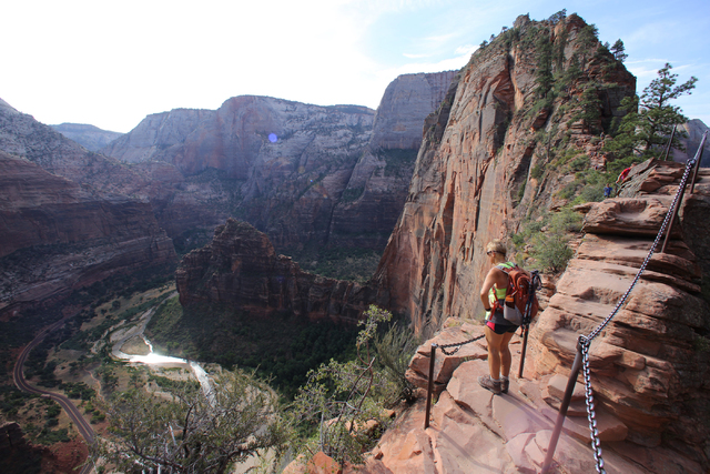 Petita Abblitt, 63, takes in the view of the canyon below while hiking Angels Landing, a 5-mile round-trip trail that climbs 1,500 feet up to the peak, in Utah's Zion National Park. (Rachel Crosby ...