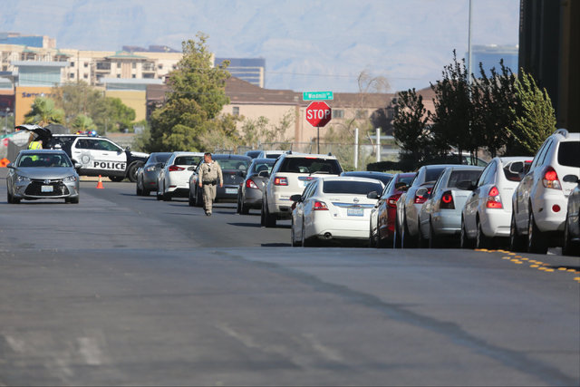 Traffic backs up near a CVS Pharmacy at the intersection of Las Vegas Boulevard and Windmill Lane, where police arrested the suspect of a shooting on I-15, in Las Vegas on Saturday, Oct. 15, 2016. ...