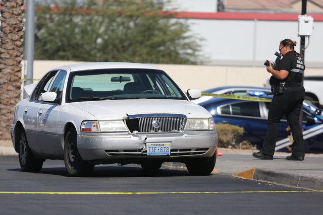 A police investigator takes photos of a sedan outside of a CVS Pharmacy where police arrested the suspect of a shooting on I-15 at the intersection of Las Vegas Boulevard and Windmill Lane in Las  ...