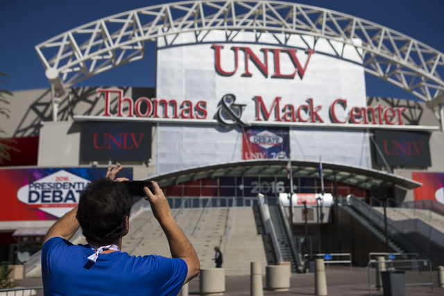 A man takes a photo of the Thomas & Mack Center ahead of the third presidential debate at UNLV in Las Vegas on Tuesday, Oct. 18, 2016. Chase Stevens/Las Vegas Review-Journal Follow @csstevensphoto