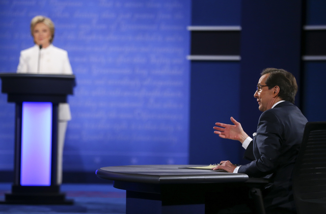 Moderator Chris Wallace of Fox News, right, poses a question to Republican presidential candidate Donald Trump, not pictured, and Democratic presidential candidate Hillary Clinton during the third ...