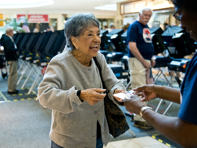 """Mary Miller, right, hands an """"I Voted"""" sticker to Renee Haga as she leaves the polls during the first day of early voting at the Galleria at Sunset in Henderson on Saturday morning, Oct. 22, 2016. ..."""