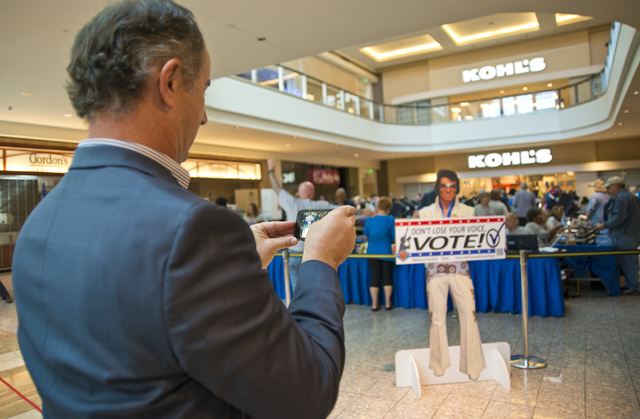 Gary Rhoades of the Nevada Democratic Party takes a photo of a stand-up Elvis sign during early voting at the Galleria at Sunset in Henderson on Saturday morning, Oct. 22, 2016. Daniel Clark/Las V ...