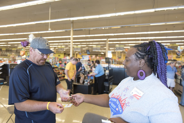 "Volunteer Ellecia Johnson, right, hands an ""I Voted"" sticker to Bart Black during early voting at Albertsons at 2885 E. Desert Inn Rd. in Las Vegas, Saturday, Oct. 22, 2016. Jaso ..."