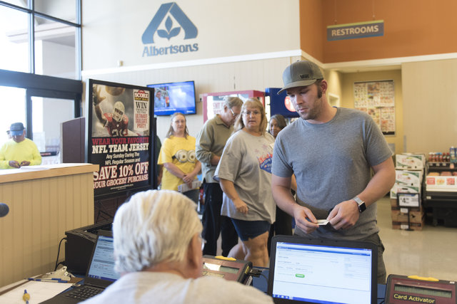 Justin Dahl, right, checks-in during early voting at Albertsons at 2885 E. Desert Inn Rd. in Las Vegas, Saturday, Oct. 22, 2016. Jason Ogulnik/Las Vegas Review-Journal