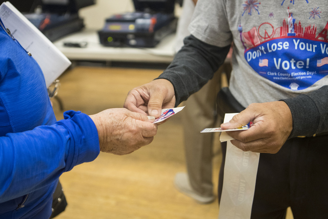 Edge worker Rudi de Leon, right, hands a voter a sticker during early voting at the East Las Vegas Community Center in Las Vegas on Saturday, Oct. 22, 2016. Loren Townsley/Las Vegas Review-Journal ...