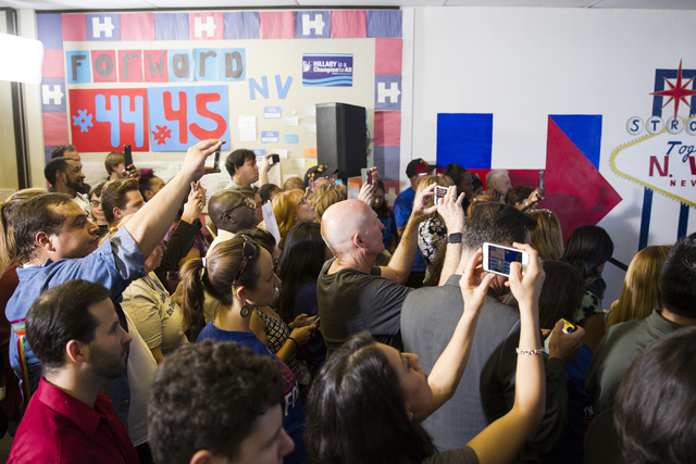 People watch former President Bill Clinton speak during an unscheduled stop to a State Democratic Party field coordinated office canvass kickoff event on Thursday, Oct. 20, 2016, in North Las Vega ...