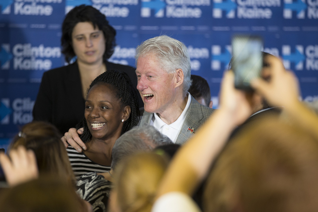 Former President Bill Clinton takes a photo with  supporters after speaking during an unscheduled stop to a State Democratic Party field coordinated office canvass kickoff event on Thursday, Oct.  ...