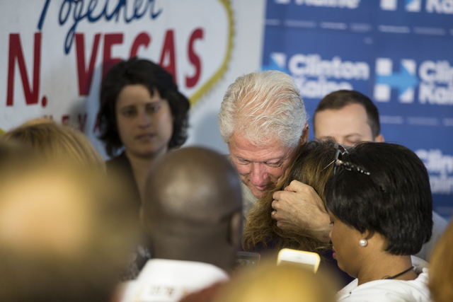 Former President Bill Clinton hugs a supporter after speaking during an unscheduled stop to a State Democratic Party field coordinated office canvass kickoff event on Thursday, Oct. 20, 2016, in N ...