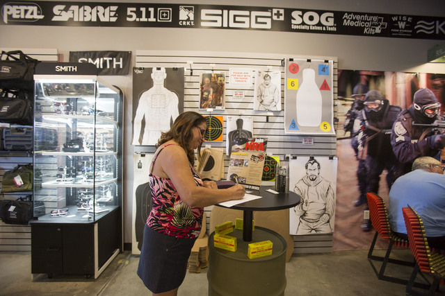 Boulder City resident Fatina Kamou applies for a background check before purchasing a handgun at Westside Armory, a gun and ammo store, located at 7345 S. Durango Drive in Las Vegas on Tuesday, Oc ...
