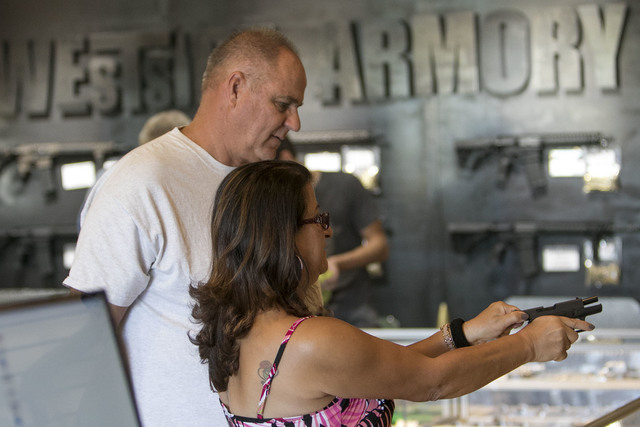 Boulder City residents Dan Laza looks on as his fianc Fatina Kamou tries out various handguns before making a purchase at Westside Armory, a gun and ammo store,  located at 7345 S. Durango Drive i ...