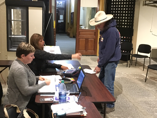 Virginia Highlands resident Larry Walker signs in to vote with Clerk-Treasurer Vanessa Stephens, left, and Deputy Clerk Treasurer Dore Nevin in the jail at the Storey County Courthouse jail on Fri ...