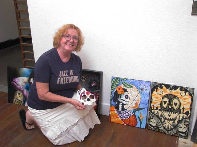 Lynne Adamson Adrian, co-owner of Wonderland Gallery in The Arts Factory, 107 E. Charleston Blvd., looks at artwork that was selected for the gallery's  Dia de Los Muertos show. It is one of sever ...