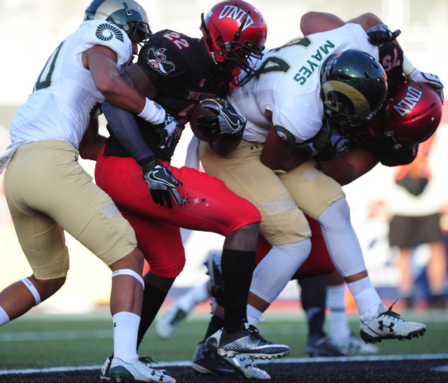 UNLV Rebels running back David Greene (22) scores a touchdown while being wrapped up by Colorado State Rams defensive back Jamal Hicks (20) in the second half of their NCAA college football game a ...