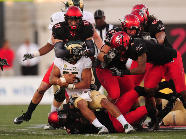 UNLV Rebels defensive back Troy Hawthorne (11) wraps up Colorado State Rams running back Izzy Matthews (35) in the second half of their NCAA college football game at Sam Boyd Stadium Saturday, Oct ...