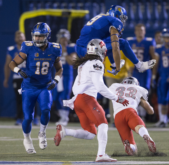 San Jose State Spartans wide receiver Justin Holmes (9) leaps over UNLV Rebels defensive back Dalton Baker (33) in their football game at CEFCU Stadium on Saturday, Oct. 29, 2016, in San Jose. Eri ...