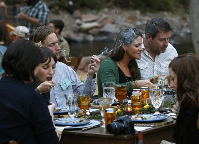Diners smoke marijuana as they eat dishes prepared by chefs during an evening of pairings of fine food and craft marijuana strains served to invited guests dining at Planet Bluegrass, an outdoor v ...