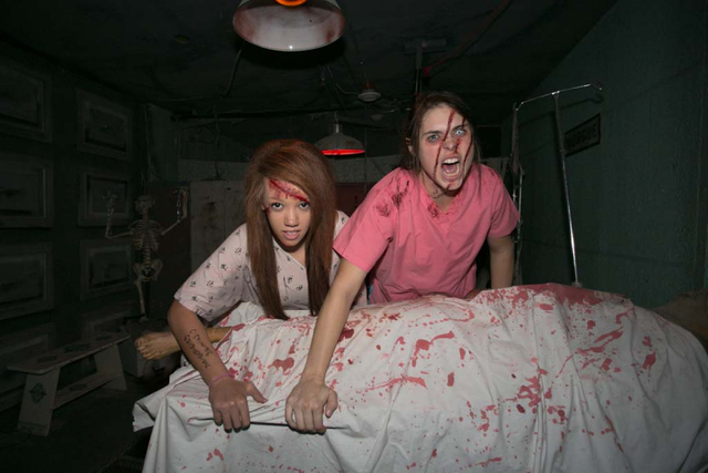 Actors Cora Setzer, right, and Shanice Taylor pose for a portrait inside The Asylum of Terror's autopsy room at the Meadows Mall in Las Vegas Oct. 3, 2013. View file photo