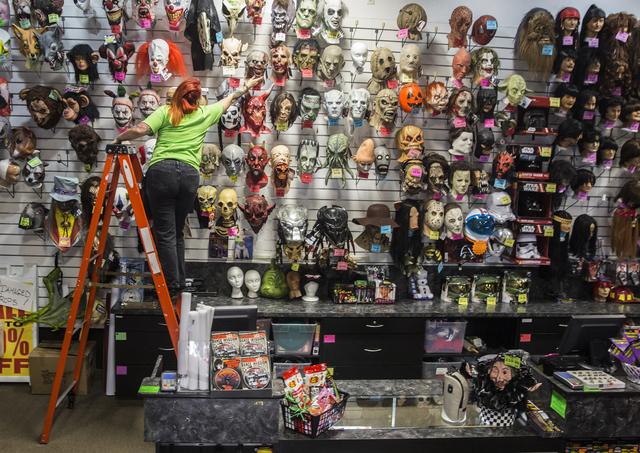 HalloweenMart employee Amber Rios straightens rows of masks Sept. 29, 2016, in Las Vegas. Benjamin Hager/View