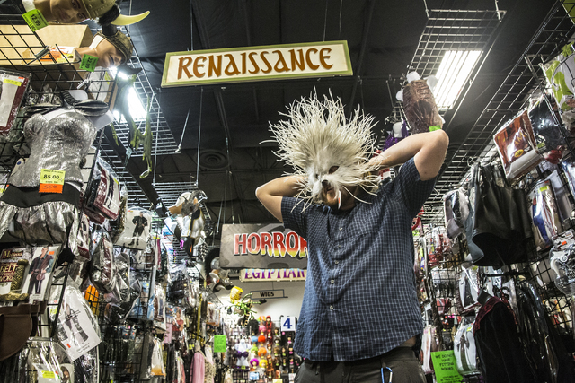 Mark Hanks tries on a mask at HalloweenMart Sept. 29, 2016, in Las Vegas. Benjamin Hager/View