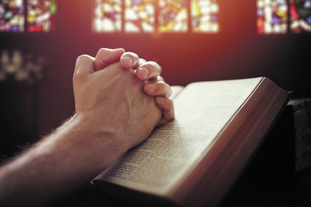 Hands folded in prayer on a Holy Bible in church concept for faith, spirituality and religion (Thinkstock)
