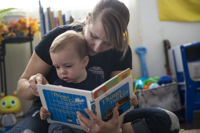 Yuliya Usyk reads with her 1-year-old son Matthew Genco at their home on Thursday, Sept. 29, 2016, in Las Vegas. Usyk, a Ukranian immigrant who grew up speaking Russian, now teaches her son the la ...