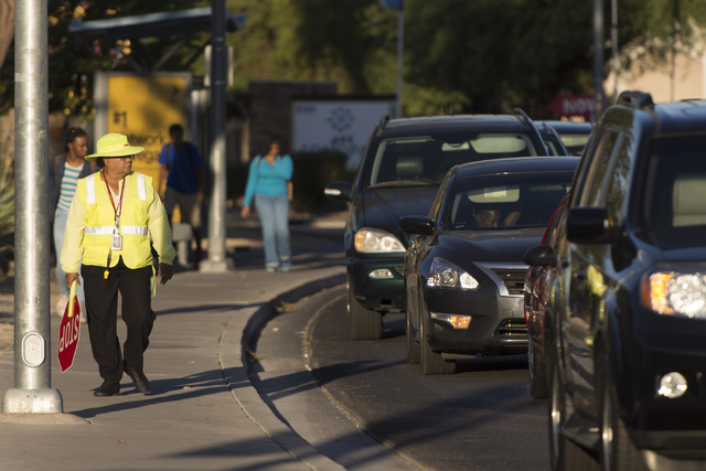 Crossing guard Patricia Bass walks to her work site at Lake Mead Boulevard and Tonopah Drive to assist children in getting to classes at West Preparatory Academy in Las Vegas, Thursday, Oct. 6, 20 ...