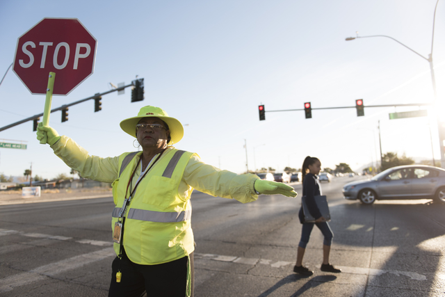 Crossing guard Patricia Bass assists a child in crossing Lake Mead Boulevard at Tonopah Drive before classes at West Preparatory Academy in Las Vegas, Thursday, Oct. 6, 2016. (Jason Ogulnik/Las Ve ...