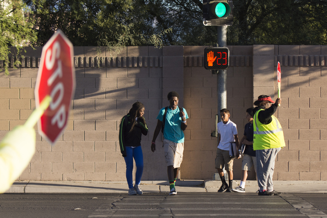 Crossing guards Rhonda Enabulele, right, and Patricia Bass assist children in crossing Lake Mead Boulevard at Tonopah Drive before classes at West Preparatory Academy in Las Vegas, Thursday, Oct.  ...