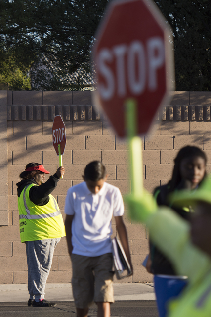 Crossing guards Rhonda Enabulele, left, and Patricia Bass assist children in crossing Lake Mead Boulevard at Tonopah Drive before classes at West Preparatory Academy in Las Vegas, Thursday, Oct. 6 ...