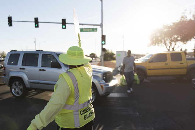 Crossing guard Patricia Bass assists a man in crossing the obstructed crosswalk on Tonopah Drive at Lake Mead Boulevard during morning rush hour in Las Vegas, Thursday, Oct. 6, 2016. (Jason Ogulni ...
