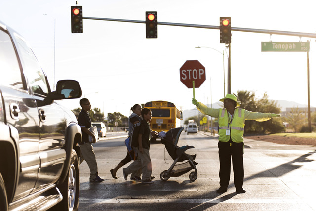 Crossing guard Patricia Bass assists children and parents in crossing Lake Mead Boulevard at Tonopah Drive before classes at West Preparatory Academy in Las Vegas, Thursday, Oct. 6, 2016. (Jason O ...
