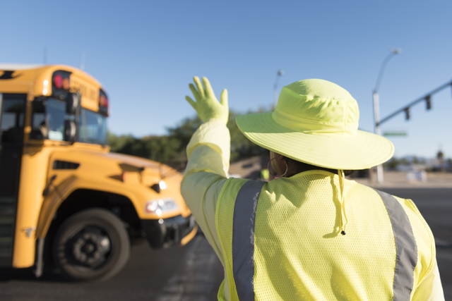 Crossing guard Patricia Bass waves to a school bus driver from her work site at Lake Mead Boulevard at Tonopah Drive before classes at West Preparatory Academy in Las Vegas, Thursday, Oct. 6, 2016 ...