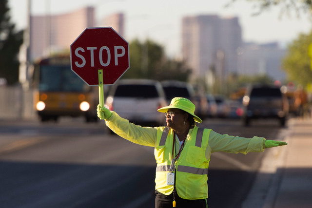 Crossing guard Patricia Bass assists children in crossing Tonopah Drive at Lake Mead Boulevard before classes at West Preparatory Academy in Las Vegas, Thursday, Oct. 6, 2016. (Jason Ogulnik/Las V ...